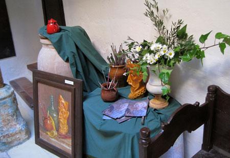 Utensilios que se usaron de modelo, pinceles, flores y un cuadro